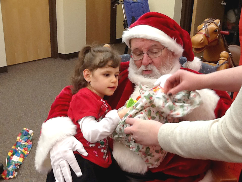 Santa holding child while opening a present